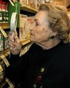 older woman using magnifier to examine products on grocery store shelf