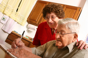 Older man writing while wife looks on encouragingly