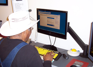 Older man using computer with large print keyboard, track ball mouse, and adjustable arm on monitor