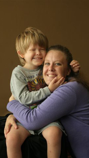 picture of visually impaired child and mother smiling and     hugging