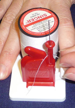 Pinch the metal foot and the thread loop between your thumb and index finger and pull your fingers away from the threading unit. You will now be holding the thread between your fingers.