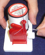 Keep pulling the thread until the end is free of the threading unit. Let go of the thread end.