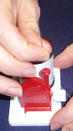 Place the tip of your index finger lightly on top of the Hold the tip of the needle between your thumb and index finger and lift it out of the funnel. As you continue to lift the needle, slide your fingers down to hold it securely by the eye; otherwise, your needle will come unthreaded as you lift..