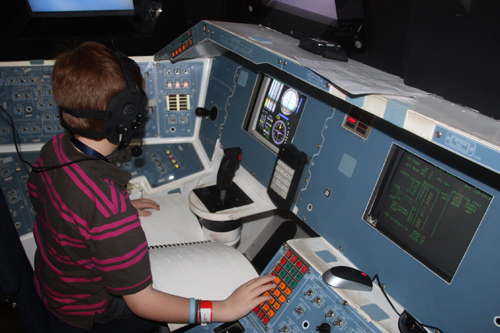child at the controls of a space shuttle Endeavor mockup, with braille manual on his lap
