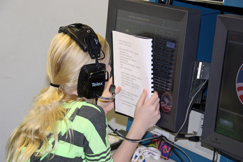 camper reads a large print manual during the space shuttle simulation
