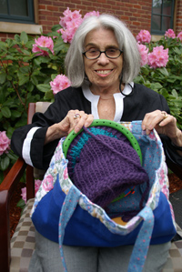 Charlotte Shrier seated outside, showing off the contents of her knitting bag