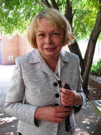 Lenore Dillon standing outside, white cane in hand