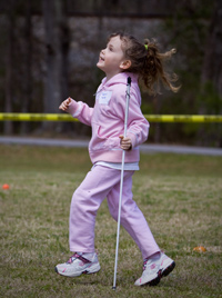 the author's daughter, gleefully running across a field with her white cane