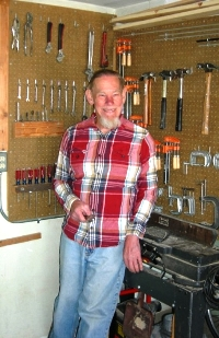 Gil Johnson standing by his tools and equipment in his workshop
