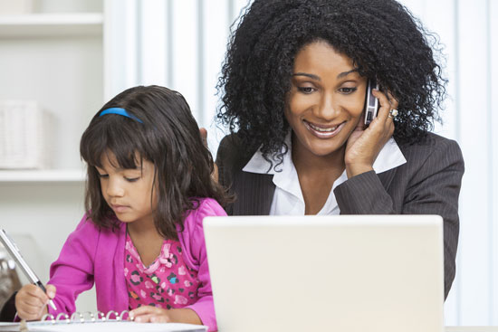 Businesswoman working on her cell phone and laptop with her daughter.