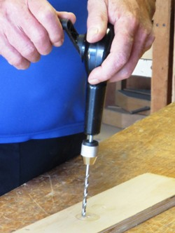Hand-operated drill in use