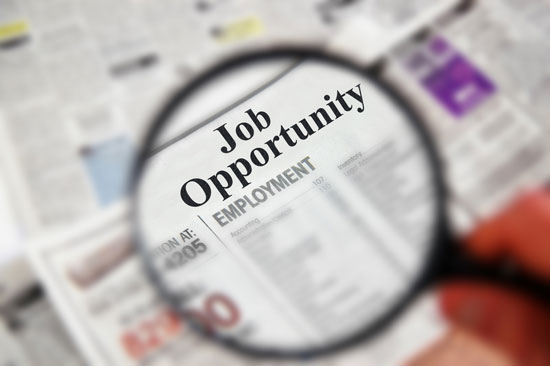 Magnifying glass over newspaper classified section with 'Job Opportunity' text