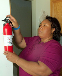 Empish Thomas grabbing a fire extinguisher from its wall mount