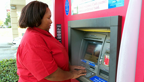 the author standing at an ATM, hands on the keypad