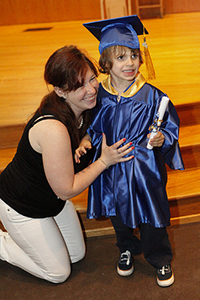 mother kneeling with her daughter, who is visually impaired, at a grade school graduation ceremony