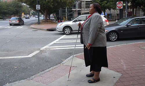 Empish standing at a street corner, white cane in hand