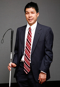 Asian man wearing a gray suit, smiling and holding white cane
