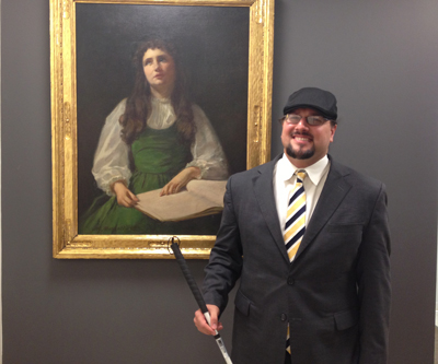 Joe Strechay in the AFB New York office in front of a portrait of Helen Keller