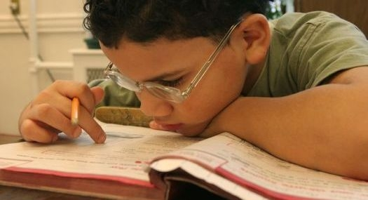 student wearing glasses leans in close to his schoolbook