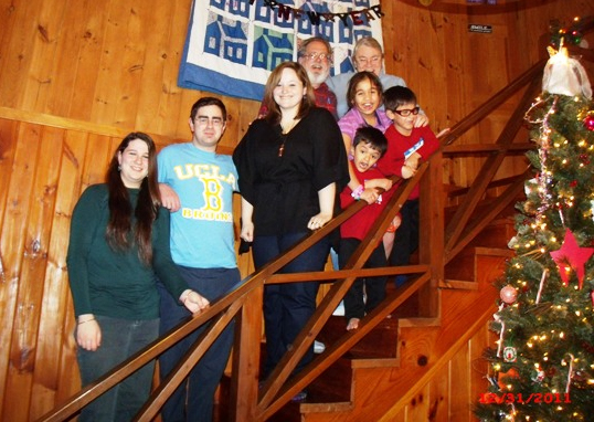 Susan Harper and family, posed on the staircase by a decorated Christmas tree
