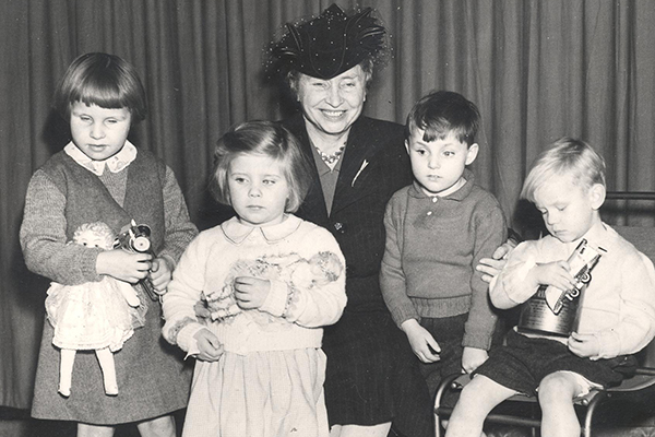 Helen Keller kneels with four children who are all holding holiday toys