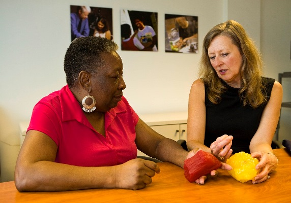 Two women seated while one of them demonstrates the difference between muscle tissue and fat using tactile examples