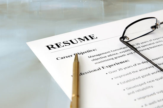 Close-up of a resume with pen and glasses on the table.