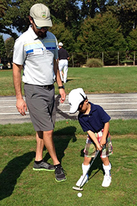 a volunteer coaches a young boy who is visually impaired and learning to play golf