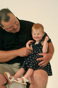 dad smiling at his young visually impaired daughter, who is sitting on his knee, smiling