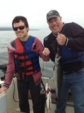 Bob and Mike, smiling and holding up the fish they caught