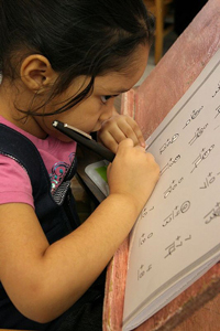 a serious young girl with low vision doing a large-print math worksheet with a black felt-tip pen