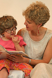 A mother reading with her visually impaired daughter