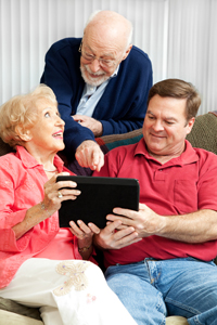 a man seated on a couch, showing an iPad to a senior couple