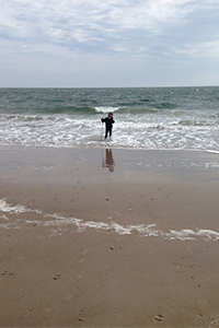 Myat enjoying the waves at Coney Island, white cane in hand
