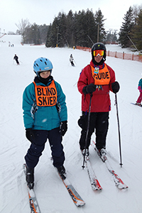 Alyssa on the slopes, wearing her BLIND SKIER vest, with a guide standing next to her