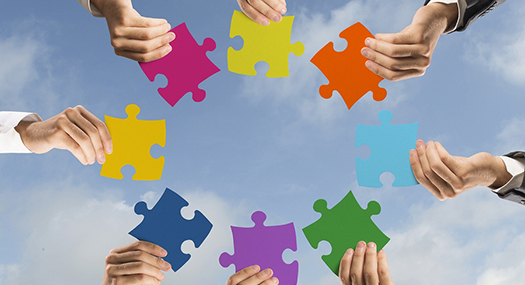 many hands reaching in with different pieces of a puzzle