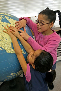 two girls touching a tactile globe in the classroom
