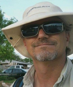 Steven wearing a hat and sunglasses, facing the viewer