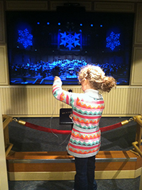 Madilyn at the Boston Children's Museum, conducting a virtual symphony!