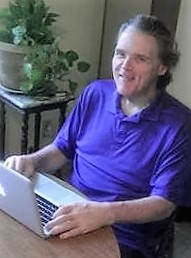 Maxwell wearing a purple shirt and smiling at the camera