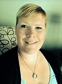 Ashley wearing blue blouse and black cardigan smiling at camera