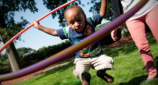 a young boy jumping, holding a hula hoop around himself