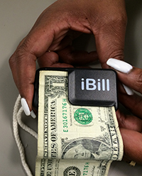 a woman's hands feeding a one dollar bill into the iBill Money Identifier