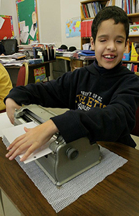 smiling boy using braillewriter in the classroom