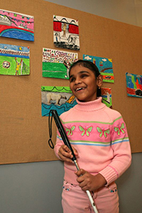 girl with white cane standing by a colorful school bulletin board
