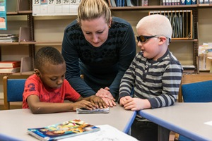 A teacher works with two children with visual impairments in a     classroom