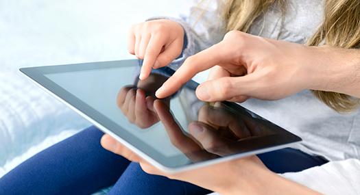 closeup of daughter and parent touching an iPad screen together