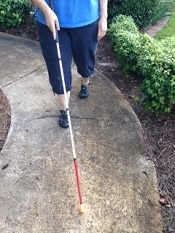 picture of person walking with long white cane extended