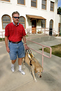 man walking with dog guide along a building's exit ramp