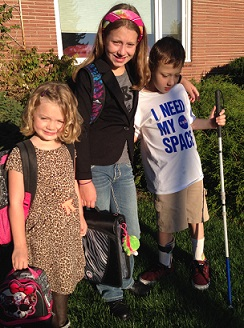 Emily Coleman's children standing together outside, prepared to head off to school